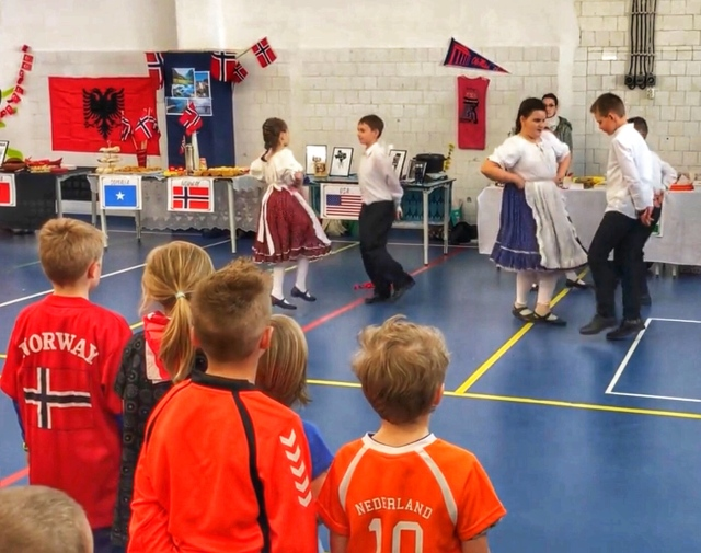 Hungarian school children performing a dance for the International Tasting event at QSI. Norwegian and Dutch school children in the foreground.