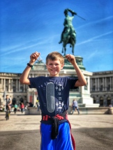 Beau with the statue of Johann Strauss Junior in the background, with the Hofburg Imperial Palace in the distance